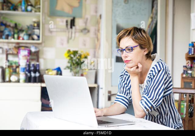 Mid adult woman working on laptop at kitchen table - Stock Image