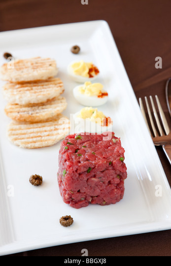 Exotic entree of bison tartare herbed potato bread deviled quail s eggs fried ox eyed capers and chervil essence - Stock Image