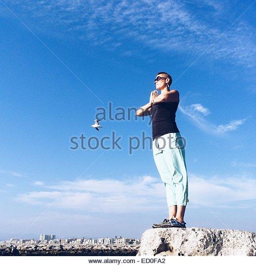 USA, California, Los Angeles, Woman meditating at edge of rock - Stock Image
