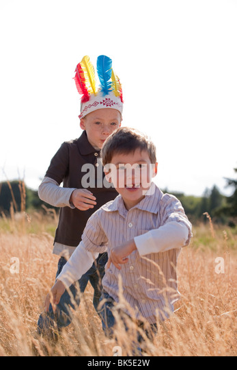 Young boys running in field - Stock Image