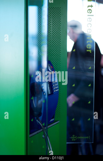 Telephone box in International airport with man in the distance - Stock Image