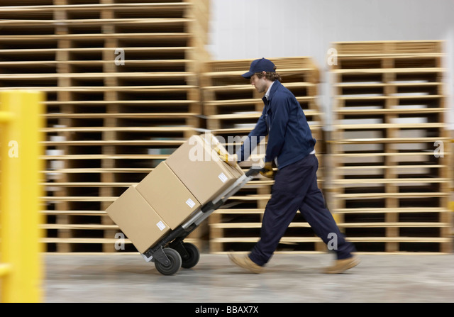 Worker pushing trolley in warehouse - Stock Image