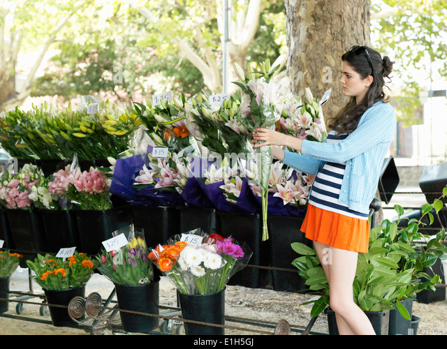 Young woman choosing cut flowers on street - Stock Image