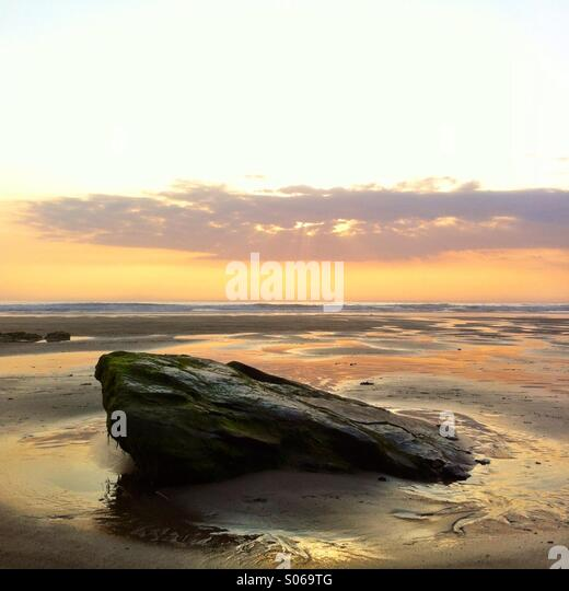 A rock at the beach at sunset. Watergate bay, newquay Cornwall England UK. - Stock Image