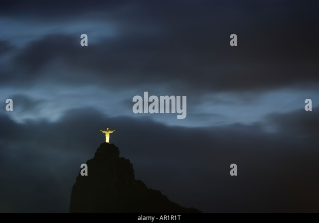 Sun setting and grey sky behind Corcovado Cristo Redentor Christ the Redeemer in Rio De Janeiro Brazil - Stock Image