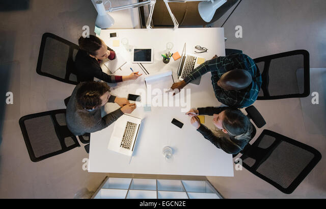 Overhead view of diverse team analyzing data while sitting at office. Multiracial business people in a meeting working. - Stock Image