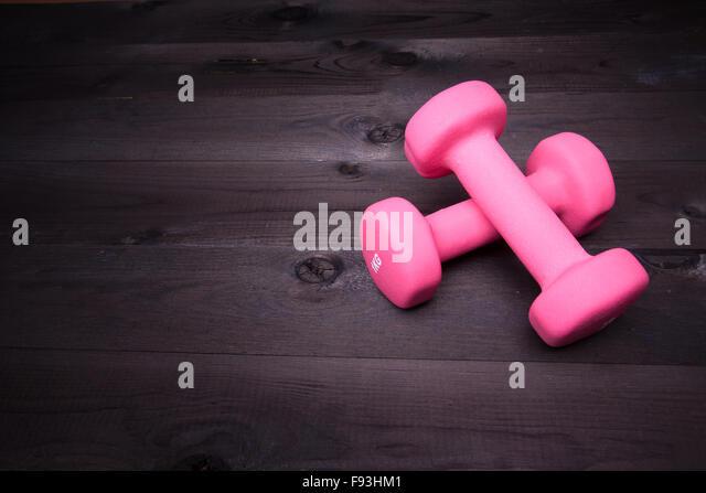 Sport equipment. Pink  dumbbell on a black wooden background - Stock-Bilder