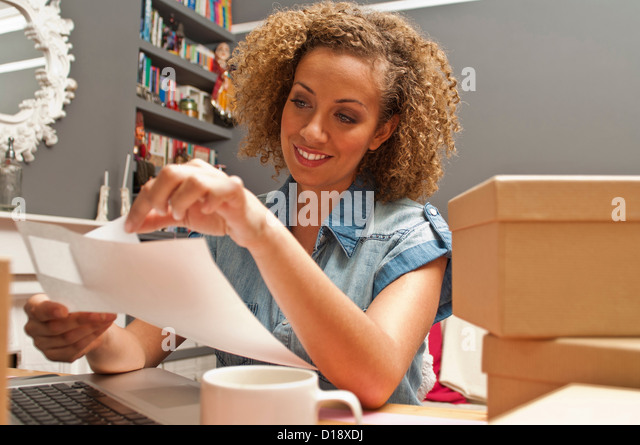 Woman sticking labels on cardboard boxes - Stock Image