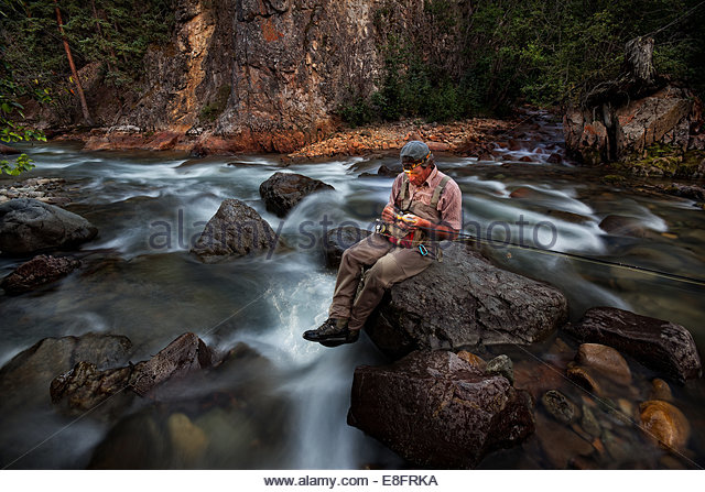 USA, Colorado, Hinsdale County, Lake City, Angler using headlamp to choose new fly - Stock Image