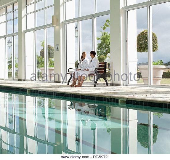 Two women sitting beside swimming pool - Stock Image