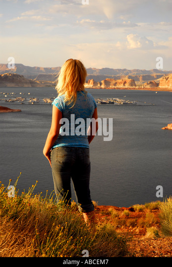 Arizona Lake Powell woman standing alone on cliff red desert mesa in background - Stock Image
