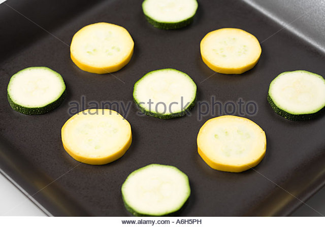 Courgette slices on a baking tray - Stock Image