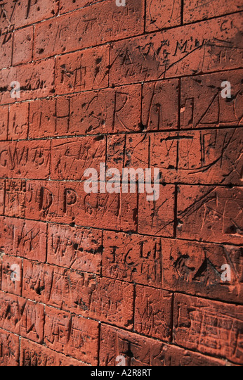 Graffiti craved in brickwork on old school walls Dedham North Essex UK - Stock Image