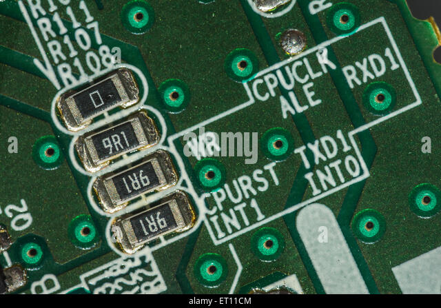 Macro-photo of printed circuit wiring for a PC motherboard. Key focus on the strip of 4 resistors to left hand side. - Stock Image
