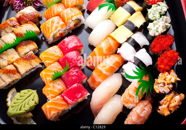 Assorted japanese sushi on a black plate. - Stock Image