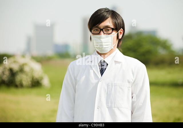 Portrait of young man wearing pollution mask and glasses - Stock Image
