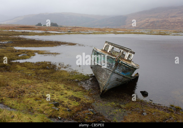 Beached fishing boat on shore at Pennyghael, Isle of Mull, Scotland. - Stock Image