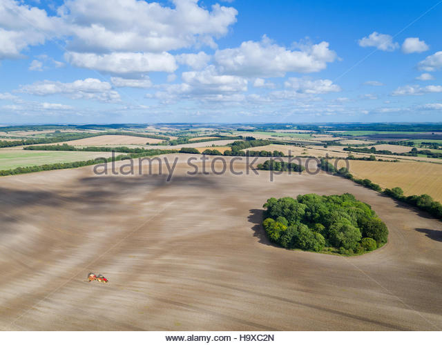 Aerial View Of Tractor Pulling Drill Sowing Wheat Seed - Stock Image