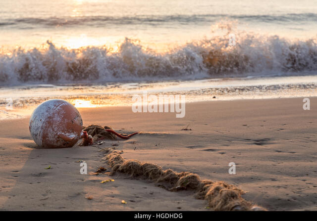 buoy and old worn rope beached on sand in bay at sunrise - Stock Image