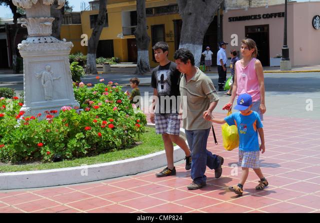 Lima Peru Barranco District urban park Parque Municipal open space garden flowers Hispanic man woman boy teen family - Stock Image