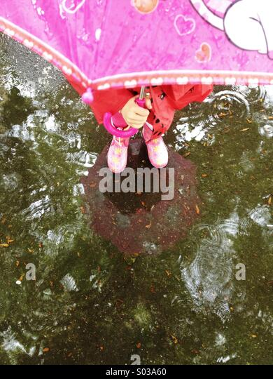 Child with umbrella standing in the puddle - Stock-Bilder