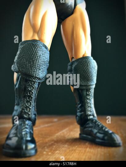 The muscular legs and boots of an action figure doll. - Stock Image