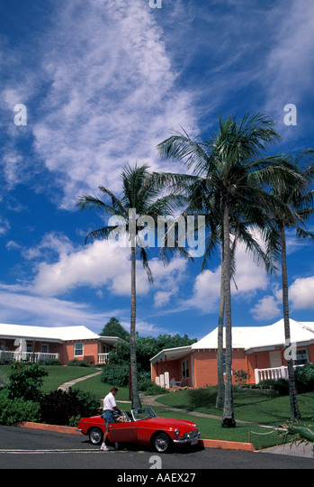 Bermuda Ariel Sands Resort pink buildings palm trees blue sky background red sports car tourist - Stock Image
