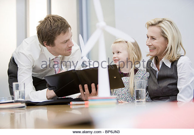Two businesspeople explaining wind technology to young girl - Stock Image