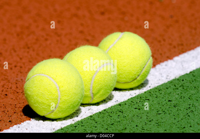 Tennis balls on a tennis court. - Stock Image