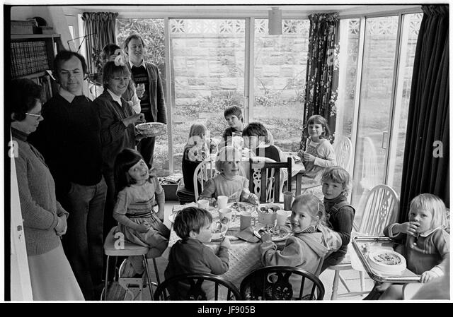Black and white picture of young cousins eating together at an extended family gathering - Stock Image