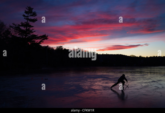 A kid skates while practicing hockey on frozen Chocolate Lake in Halifax, Nova Scotia, Canada,  January, 2012. (Adrien - Stock Image