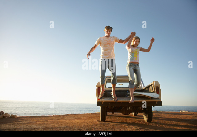 Young couple jumping from back of van parked by ocean - Stock Image
