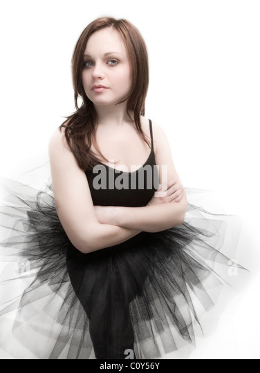 Portrait of a teenage dancer wearing a black tutu against a white background. - Stock Image