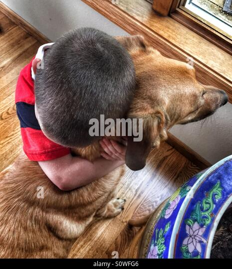 Young boy hugging his pet dog - Stock Image