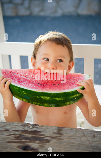 Little boy eating big slice of watermelon - Stock Image