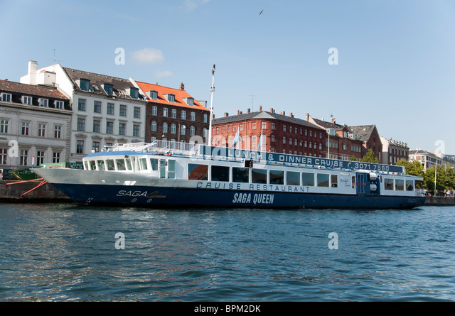 A view of the buildings and a canal cruise boat on the Nyhavn canal in Copenhagen, Denmark. - Stock Image