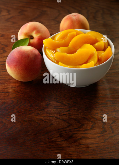 Bowl of fresh peeled peaches - Stock Image