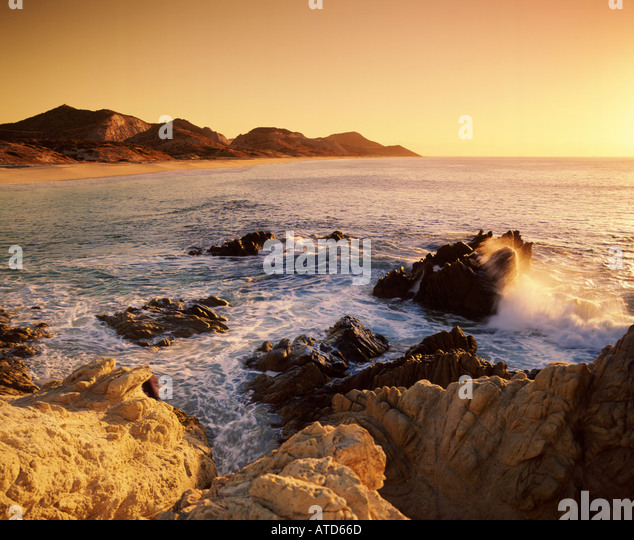 Waves crash onto the rocky shore of Cabo San Lucas Mexico in the late afternoon - Stock Image