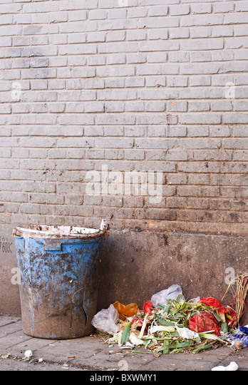 garbage besides a trash bin in a back alley - Stock Image