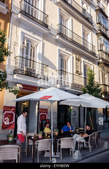 Spain Europe Spanish Madrid Recoletos Salamanca Taberna Embroque outside alfresco Hispanic man friends - Stock Image