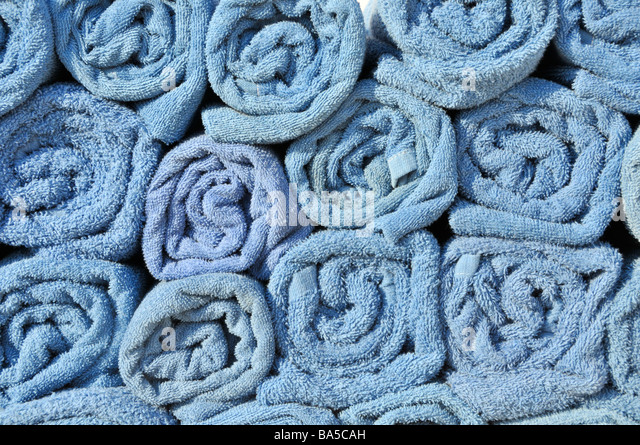 On board cruise ship end on view of clean rolled uo towels in rack available for passengers to place on sun loungers - Stock Image