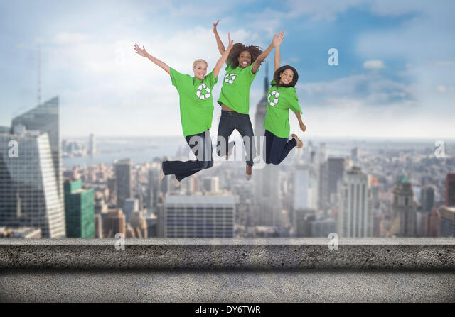 Composite image of enviromental activists jumping and smiling - Stock Image