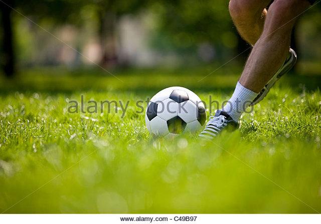 A young man kicking a football outdoors - Stock Image