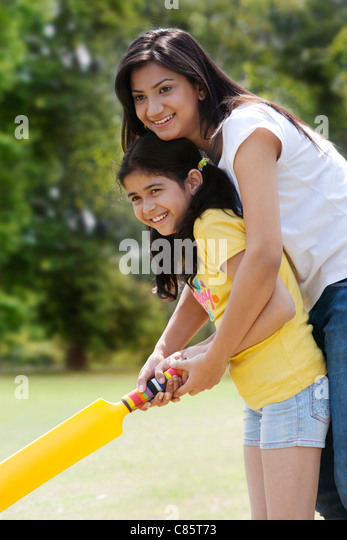 Mother and daughter playing cricket - Stock Image