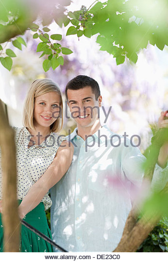 Couple sitting together outdoors - Stock Image
