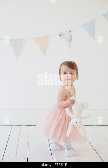 Young girl holding a cuddly toy, standing in a photographers studio, posing for a picture. - Stock Image