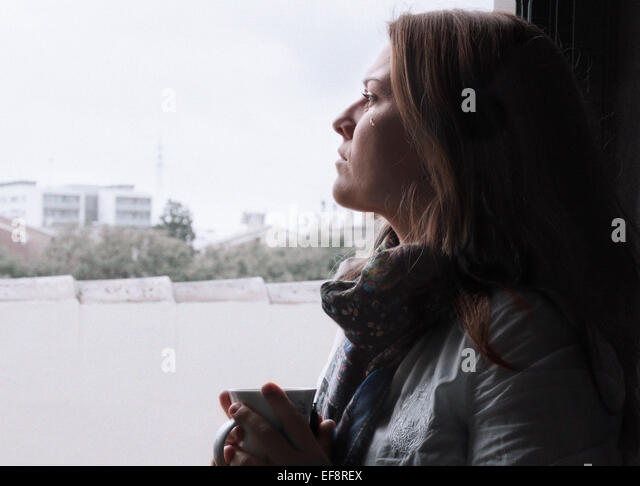 Crying woman looking through window - Stock Image