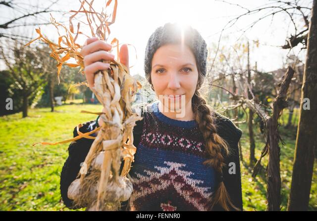Young woman in garden holding freshly picked garlic bulbs looking at camera smiling - Stock Image