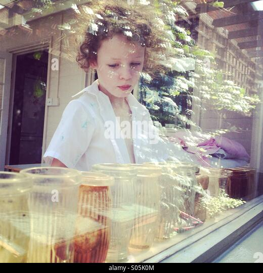 Thoughtful girl behind window with reflections - Stock Image