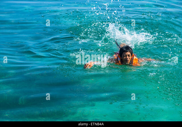 Teenage boy wearing a life jacket swimming in the sea, Salakan Island, Semporna, Sabah, Malaysia - Stock Image